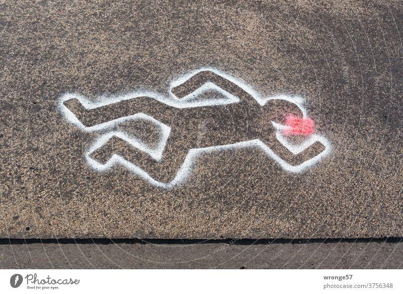 Tatort Straße | mit weißer Sprühfarbe auf schwarzem Asphalt markierte Umrisse einer auf der Straße liegenden Person schwarzer Asphalt Weiße Farbe umrissen