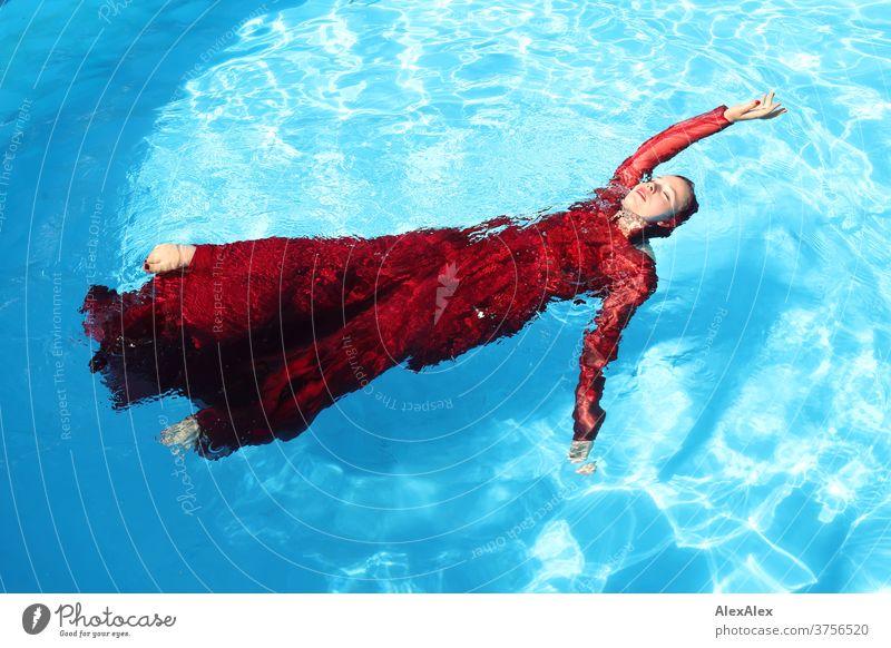 Junge Frau in rotem Ballkleid liegt mit ausgestrecktem Arm in einem Swimmingpool junge Frau Mädchen schön anmutig sportlich schwimmen Sonnenlicht Sommer Pool