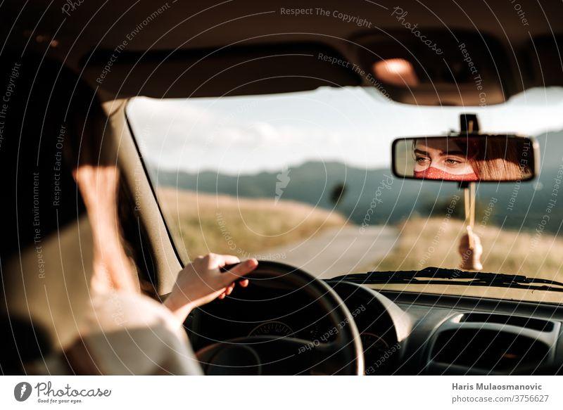 Frau mit Maske fährt Auto, Gesicht im Rückspiegel, reist in der 19. Abenteuer Automobil PKW Coronavirus covid-19 Laufwerk Fahrer Gesichtsmaske Hand im Auto