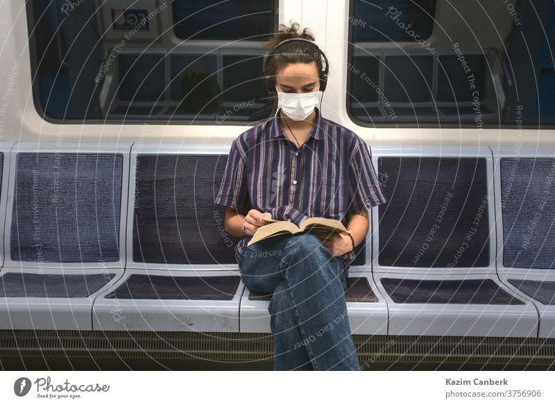 Konzentriert maskiert tausendjährig ein Buch lesen und in der U-Bahn Musik hören unterirdisch Mundschutz Kopfhörer Sitzen Mann jung Schüler Teenager Universität
