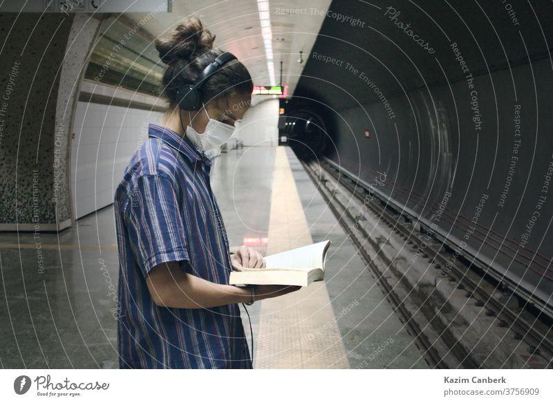 Maskierter Teenager mit Kopfhörer-Lesebuch beim Warten auf die U-Bahn unterirdisch Mann jung Schüler tausendjährig Universität Hochschule Erwachsener Mundschutz