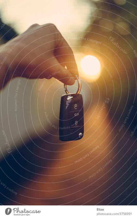 Eine Hand hält einen Autoschlüssel ins Gegenlicht Führerschein autokauf hand straße halten kaufen neues auto führerscheinprüfung bestanden autofahren warm