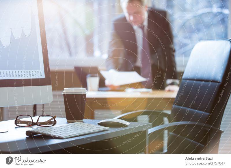 Nahaufnahme eines Büroschreibtisches mit Computer, Tastatur, Brille und Tasse Kaffee. Geschäftsmann im Anzug arbeitet mit Dokument im Hintergrund Schreibtisch