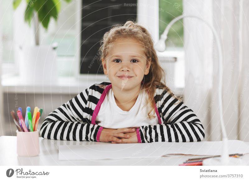 Porträt eines charmanten kleinen Mädchens, das an einem Tisch sitzt. Das Mädchen sitzt am Tisch, auf dem Tisch liegt ein Skizzenbuch, Buntstifte. Hausaufgaben, Hausunterricht, soziale Distanz