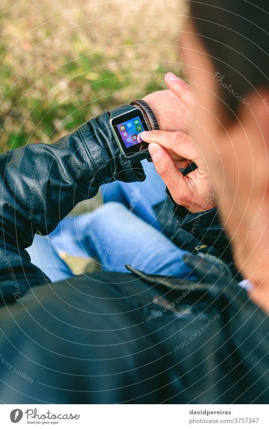Unbekannter junger Mann benutzt seine Smartwatch unkenntlich Hand smartwatch berührend zuschauen Zeigen tragbar Technik & Technologie Blick Mitteilung