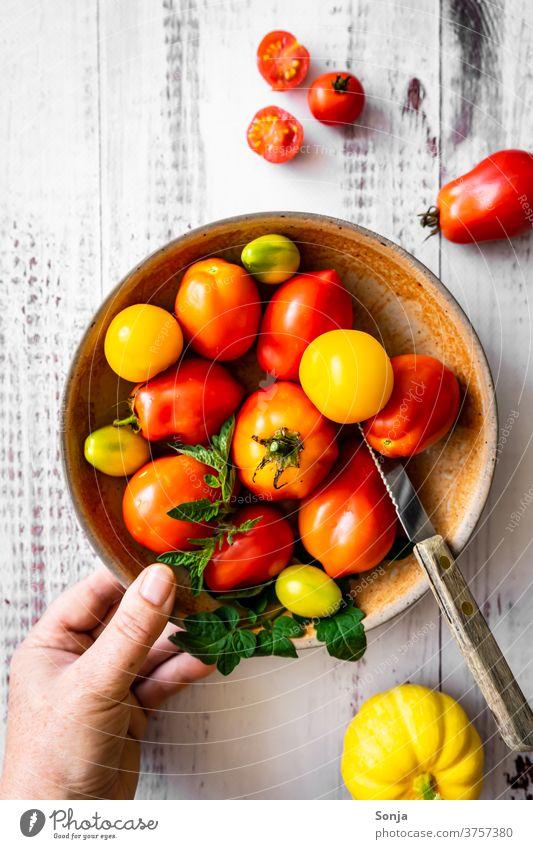 Hand mit einem Teller voller roher Tomaten auf einem Holztisch. Draufsicht, gesunde Ernärhung. rot halten Messer Gemüse Farbfoto Ernährung Gesunde Ernährung