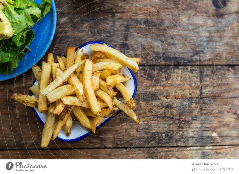 Pommes Frites mit Avocado und Senfsalat Fries Französisch Kartoffel Chips Salatbeilage Blätter Lebensmittel gelb Snack schnell braten hölzern golden essen