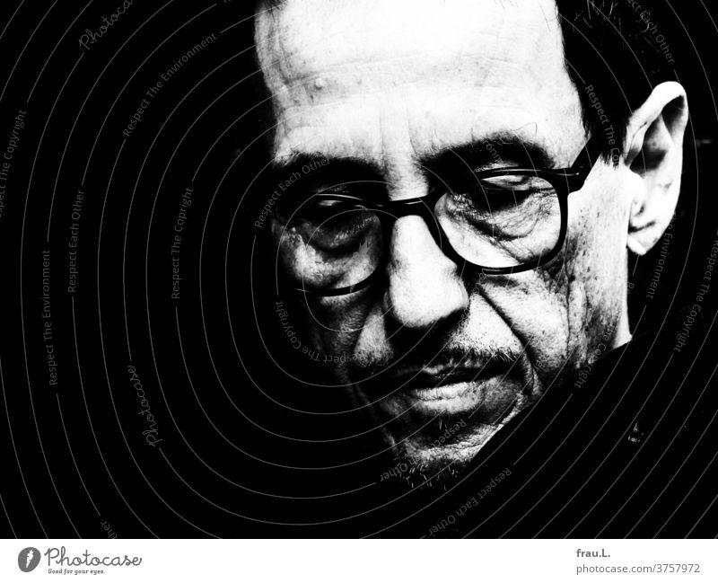 In sich gekehrt senkte der Mann die Augen und folgte seinen Gedanken. Porträt Gesicht Brille Kragen denken grübeln Bart