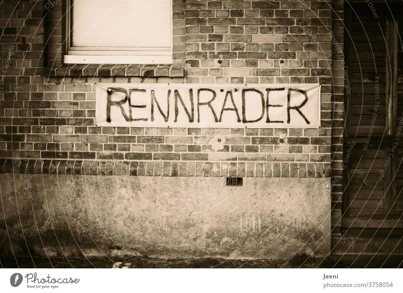 """Gemauerte Wand in einer Stadt mit dem Banner """"RENNRÄDER"""" Stein gemauert Mauer Rennräder Rennrad Schild Rad Ziegelstein rot alt retro verlassen verlassenes haus"""