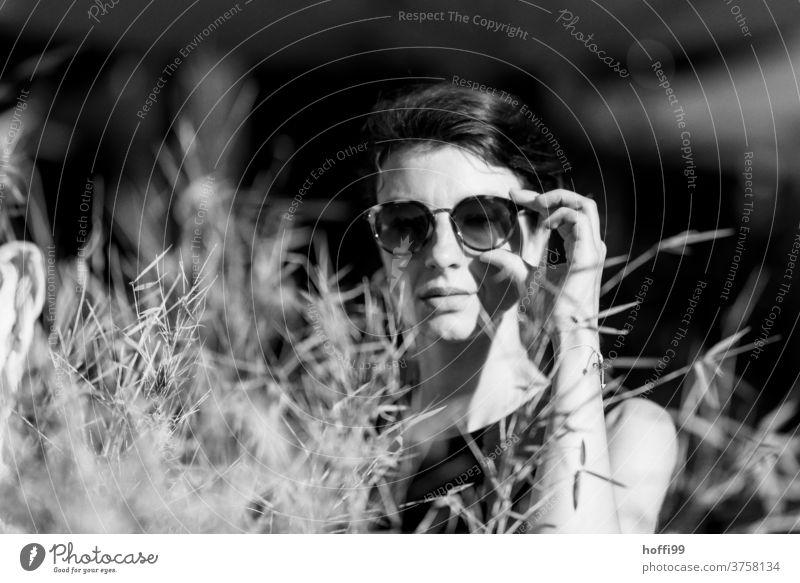 überrascht blickt die Frau in die Kamera und greift zur Sonnenbrille nachdenklich portraite Frauengesicht Erwachsene 18-30 Jahre feminin Frauenaugen schön