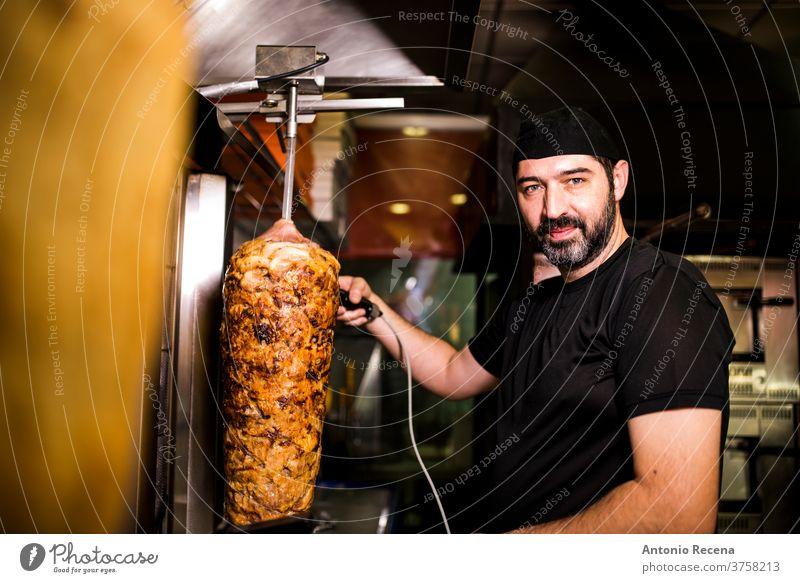 Bärtiger Mann, der in einer Pizzeria Kebab-Fleisch zubereitet. Türkisch Erwachsener Person Menschen Lifestyle attraktiv Männer männlich bärtig Verkäufer Laden