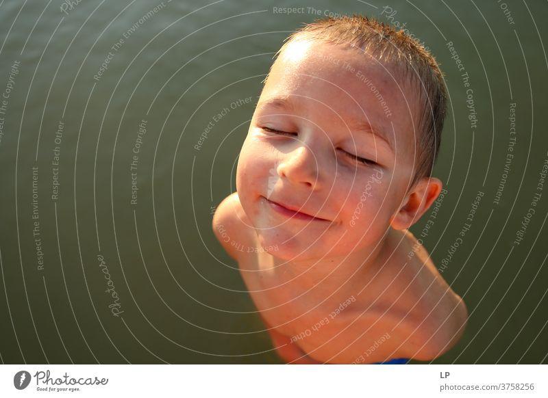 Schöner Junge, der der Sonne zugewandt ist, die Augen geschlossen geschlossene Augen Vorderansicht Oberkörper Porträt Sonnenstrahlen Kontrast Schatten Licht