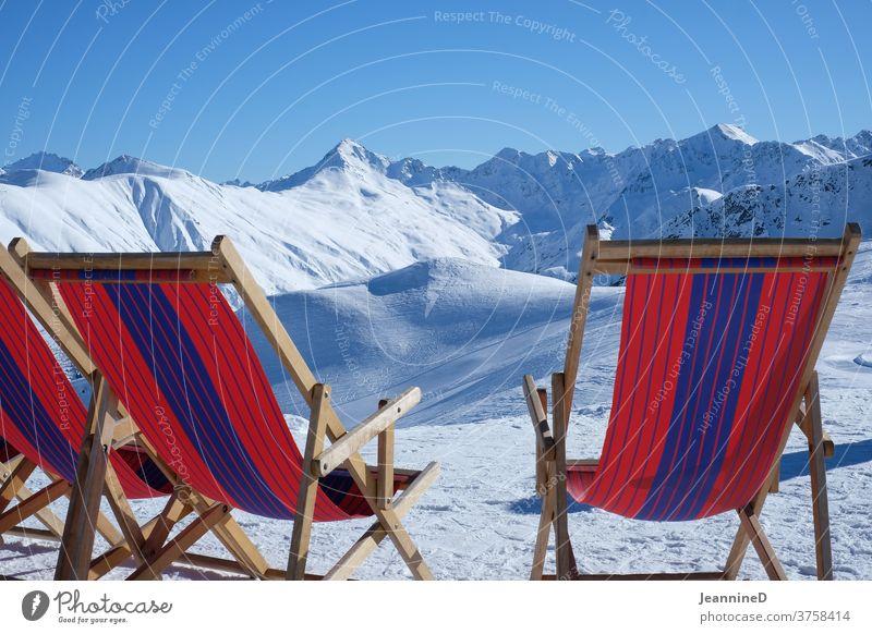 drei Liegestühle rotblau in einer Winterlandschaft Liegestuhl gestreift Winterurlaub Winterstimmung Schnee Farbfoto Außenaufnahme Schneelandschaft Natur
