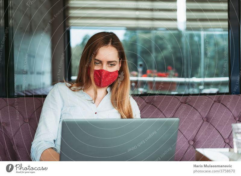 Freiberuflerin mit Gesichtsmaske arbeitet am Laptop im Café Erwachsener attraktiv schön Business Geschäftsfrau Kaffee Kaffeehaus Mitteilung Coronavirus