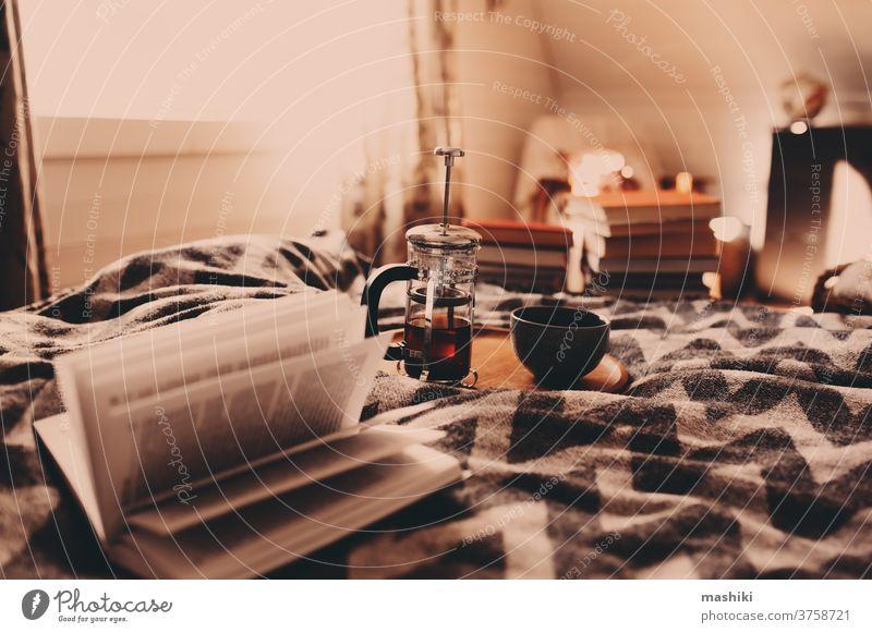 Gemütlicher Wintermorgen mit einer Tasse heißem Tee. Nordisches Schlafzimmer-Interieur in ländlichem Holzhaus oder Hütte, Hygge-Konzept gemütlich heimwärts warm