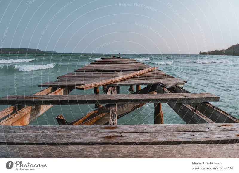 Die filmische Sommer-Kulisse eines zerbrochenen Holzstegs vor dem weiten blauen Meer auf der Insel Sok San Beach Koh Rong in Kambodscha zeigt das Konzept der Unterstützung von psychischer Gesundheit, sozialer Isolation und sozialer Distanzierung während der Covid-19-Pandemie