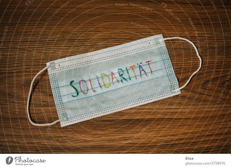 Corona Thoughts | Eine Maske auf der das Wort Solidarität steht. Maskenpflicht Mundschutz Schutz bunt Buchstaben geschrieben Infektionsgefahr COVID Coronavirus