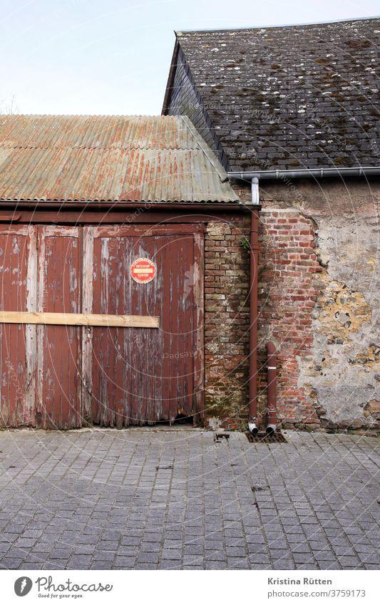 altes haus trifft auf alte garage mit französischem parken verboten schild scheune schuppen hof einfahrt zufahrt garagenausfahrt freihalten holztor garagentor