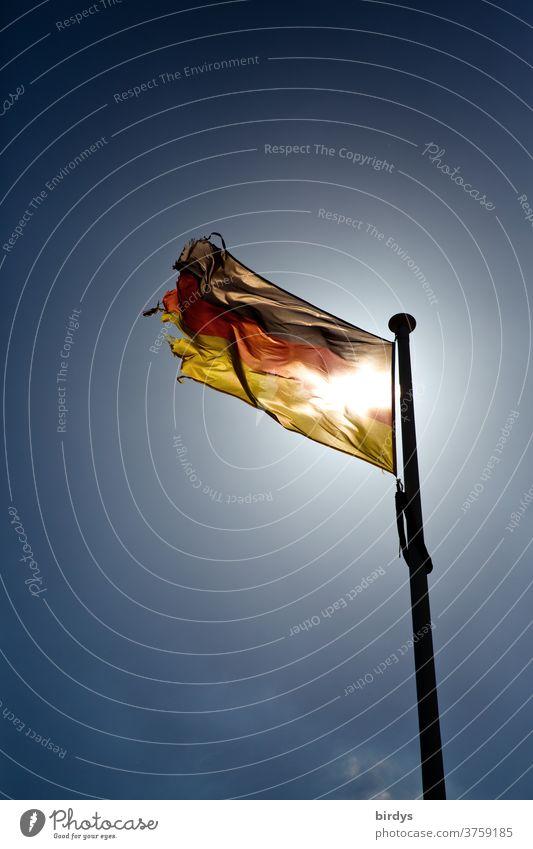 wehende , leuchtende Deutschlandflagge mit durchscheinender Sonne leuchtet im Gegenlicht vor wolkenlosem Himmel. Deutschlandfahne, schwarz-rot gold