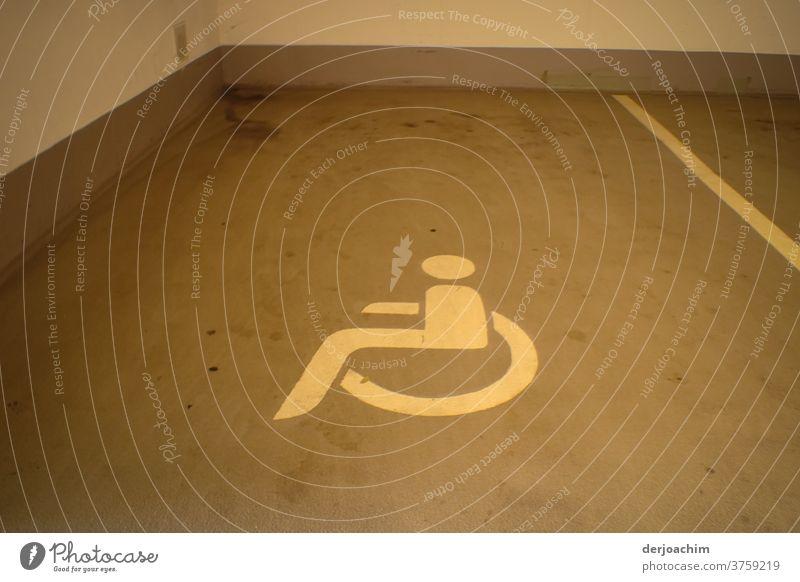Reserviert für Behinderte ist der  Parkplatz in der Tiefgarage. Mit einem auf dem Boden gezeichnetem   liegendem Rollstuhl Bild. Garageneinfahrt Parkhaus parken