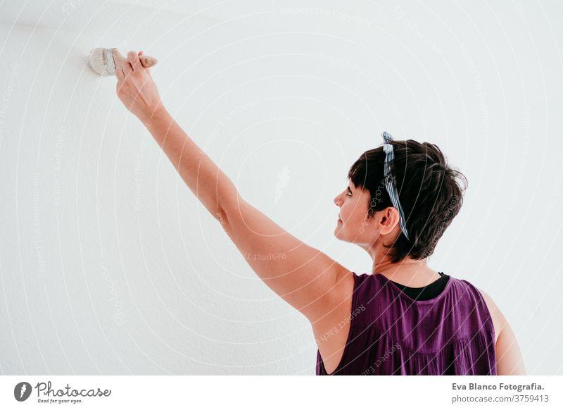 glückliche kaukasische Frau, die die Zimmerwände mit weißer Farbe streicht. Do it yourself und neues Wohnkonzept Kaukasier Malerei heimwärts Haus Bürste Glück