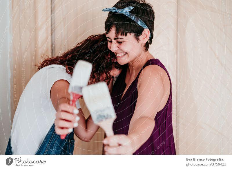 glückliches lesbisches Paar, das die Zimmerwände mit weißer Farbe streicht. Do it yourself und neues Wohnkonzept Freunde Frauen bewegend heimwärts Haus