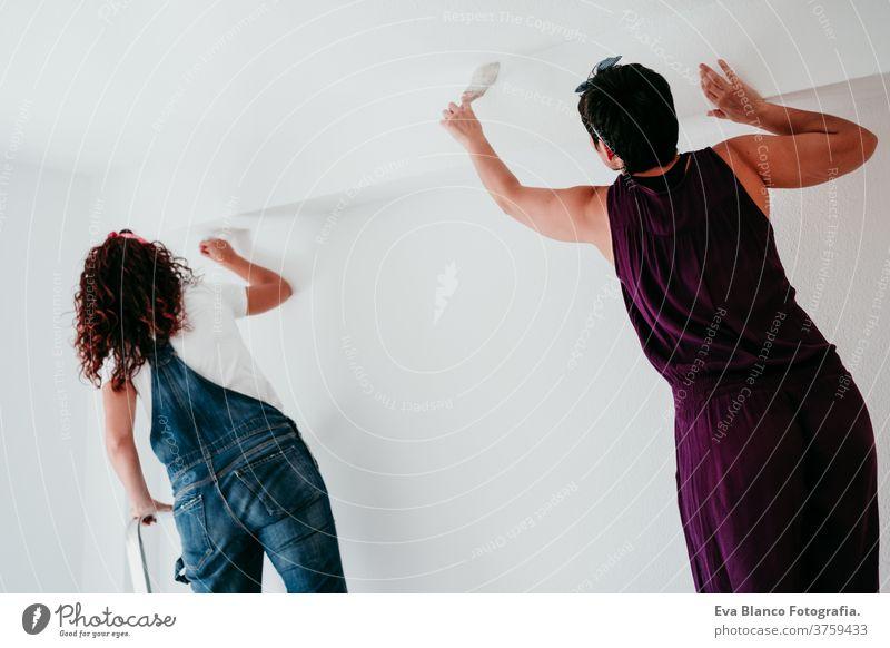 lesbisches Paar, das die Zimmerwände mit weißer Farbe streicht. Do it yourself und neues Wohnkonzept Freunde Frauen bewegend heimwärts Haus es selbst machen