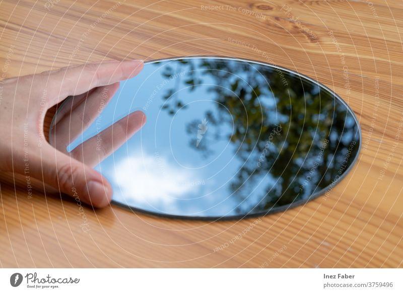 Runder Handspiegel auf einem Tisch, Spiegelung eines Baumes, Wolken und blauer Himmel Windstille den Himmel einfangen Wolkenreflexion Cloud Baumreflexion
