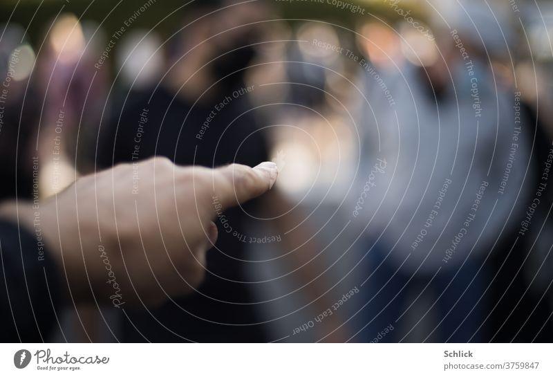 Hand deutet mit Zeigefinger auf völlig unscharfe Person  -  mit dem Finger auf jemanden zeigen Unschärfe Mensch geringe Tiefenschärfe Lichtkreise Gegenlicht