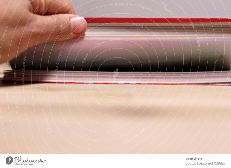 Hand blättert durch ein Buch, das auf einem Tisch liegt. Roter Einband. Literatur, lesen, Bildung blättern hand bildung einband hobby rot literatur roman Papier
