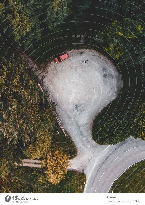 Auto und Mensch von oben Caddy Camping Wild Camping liegen Parkplatz Schneeengel Fläche Drohnenansicht Vogelperspektive Wald grün Baum Natur Abenteuer Strasse