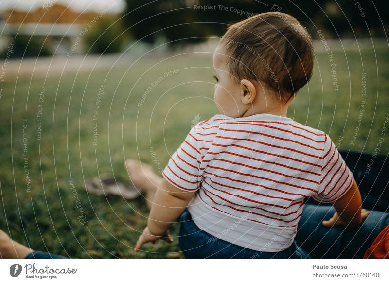 Kleinkind sitzt auf dem Rasen und schaut weg Kind Sitzen Gras Frühling Frühlingsgefühle Sommer Sommerurlaub Fröhlichkeit Tag Mensch Kindheit Farbfoto Wiese