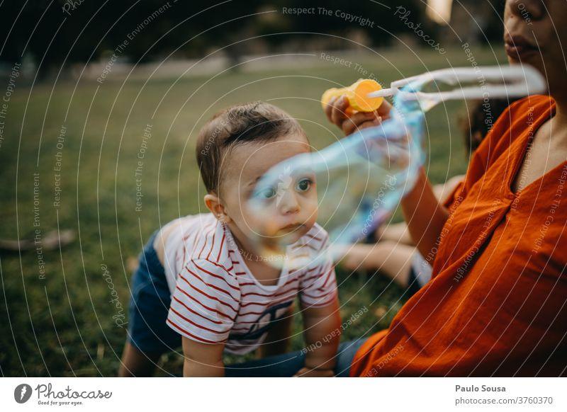Mutter und Kind spielen mit Seifenblasen Spielen Freizeit & Hobby Mutterschaft Kleinkind im Freien Kaukasier authentisch Lifestyle Leben Farbfoto Glück
