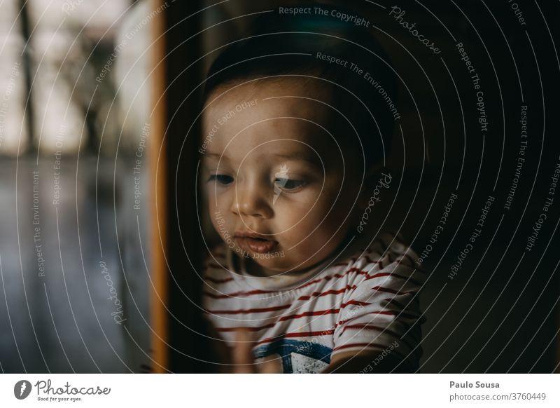 Kind am Fenster Kindheit Kleinkind zu Hause Innenaufnahme Gesicht Junge Interesse Tag Familie & Verwandtschaft Quarantäne Farbfoto zu Hause bleiben Nahaufnahme