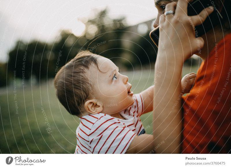 Kleiner Junge beobachtet Mutter am Telefon Kommunizieren Mitteilung Drahtlos Smartphone Mutterschaft Mutter mit Kind Kleinkind Baby 0-12 Monate