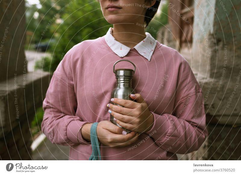 Frau in rosafarbenem Sweatshirt hält nachhaltige Öko-Flasche aus Metall mit ihren Händen im Freien, selektiver Fokus Nahaufnahme Finger Beteiligung Mädchen