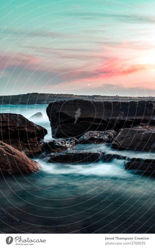 Wellen stürzen bei Sonnenuntergang in Marourbra in Sydney, Australien, über Felsen Meer rosa Frühling nsw newsouthwales Ostküste Strand Steine Sommer blau