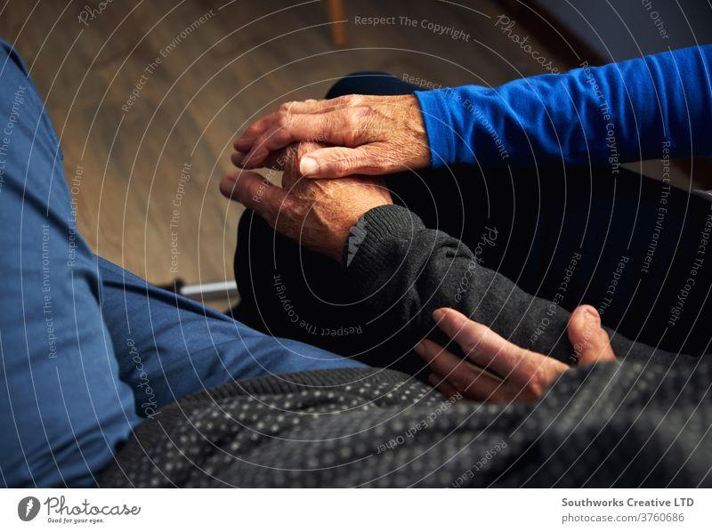 Älteres Ehepaar hält Hände auf dem Sofa Senior Pflege alt Beteiligung Liebe Mann knittern aussruhen Erholung heimwärts binden Menschen Lifestyle im Innenbereich