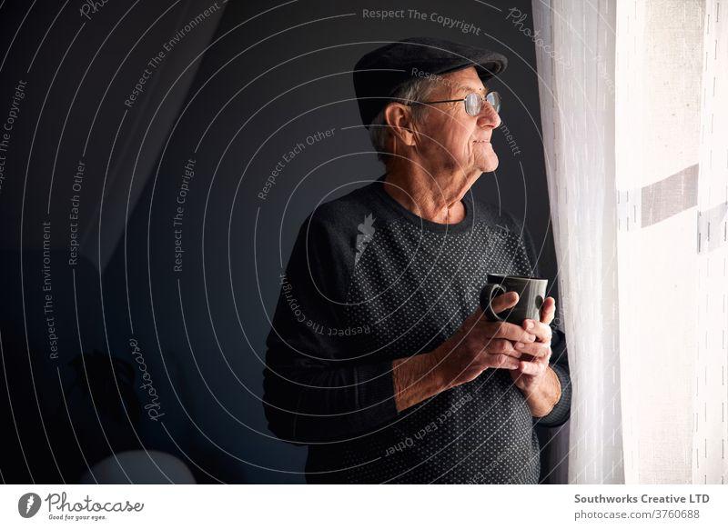Älterer Mann lächelt aus dem Fenster Senior männlich Hut Brille heimwärts Glück Lächeln Blick Textfreiraum in den Ruhestand getreten Kaffee Becher Tasse Warten