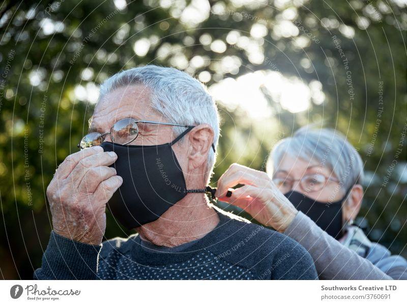 Aktives Seniorenpaar beim Spaziergang im Freien mit Gesichtsmasken älter Paar Mundschutz deckend reif Glück Liebe in den Ruhestand getreten aktiv Kaukasier