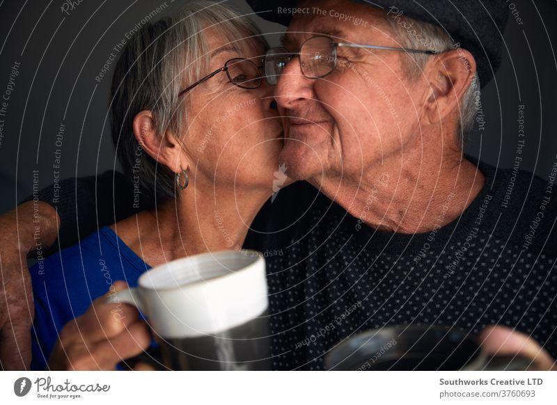Glückliches älteres Paar, das sich küsst und lacht Senior Küssen Lächeln Lachen 70 70's Kuss Hipster Reife grauhaarig ältere Menschen Babyboomer liebevoll