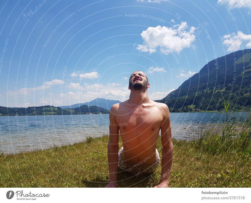 junger Mann macht Körper Gymnastik an einem See Dehnungsübung Yoga Gesundheit Oberkörper Fitness Sport maskulin Sport-Training Sportler im Freien muskulös