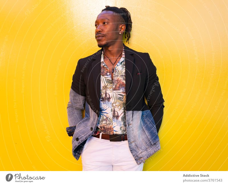 Selbstbewusster ethnischer Mann in stilvoller Kleidung in der Stadt Model ausgefallen Stil Bekleidung Großstadt lebhaft gelb Wand trendy männlich schwarz