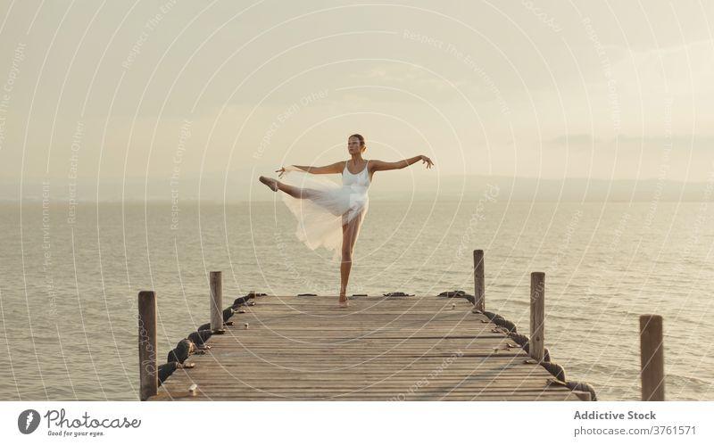 Schlanke Ballerina tanzt auf Strandpromenade in der Nähe von Meer Anmut Tanzen MEER Promenade beweglich klassisch Balletttänzer elegant Pose Sonnenuntergang