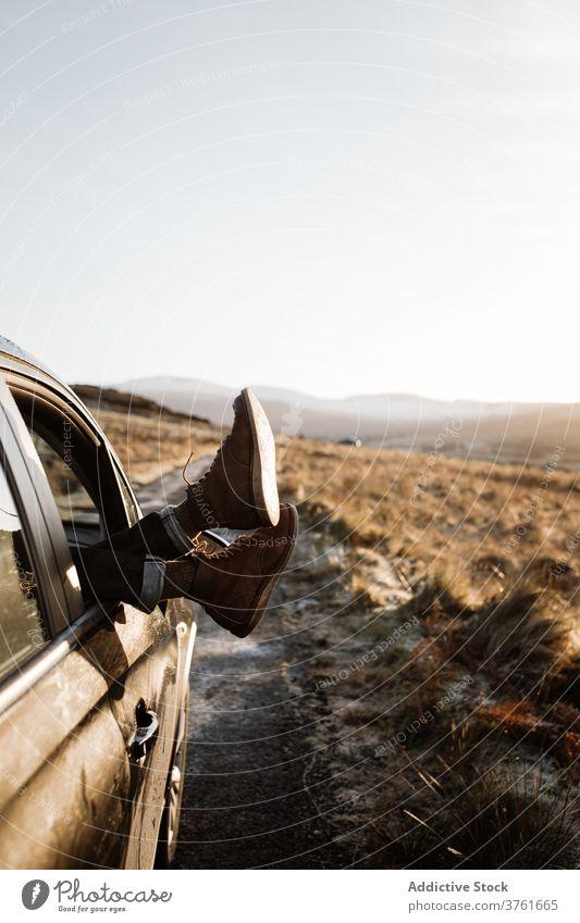 Crop Reisende entspannen im Auto in den Bergen Reisender PKW Bein Fenster Berge u. Gebirge sich[Akk] entspannen Sonnenaufgang Hochland Autoreise