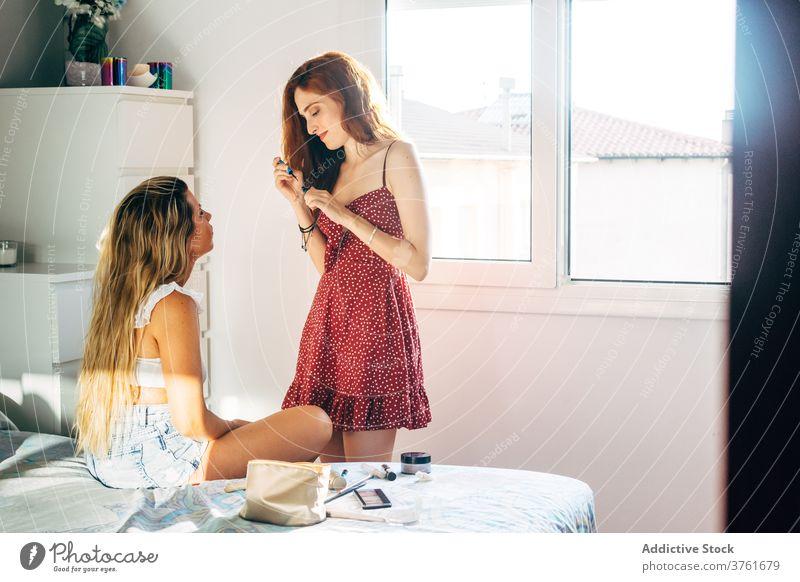 Fröhliche Freundinnen beim Schminken zu Hause Make-up heimwärts Frauen Pulver Bürste Lachen Zusammensein Gesicht Schönheit heiter Glück Lächeln Optimist feminin