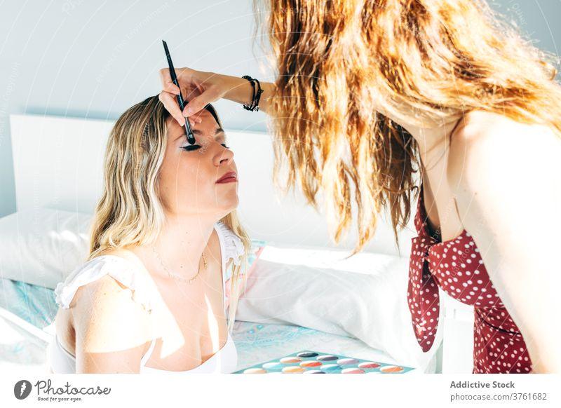 Crop Frau tun Make-up im Studio Lidschatten bewerben Gesicht Künstler Frauen Schönheit Salon Kosmetik dekorativ Klient hell Kunde Bürste professionell elegant