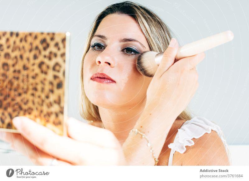 Frau Anwendung Make-up zu Hause Pulver Bürste bewerben heimwärts Kosmetik Schönheit Routine charmant perfekt Hautpflege Glamour natürlich Pflege