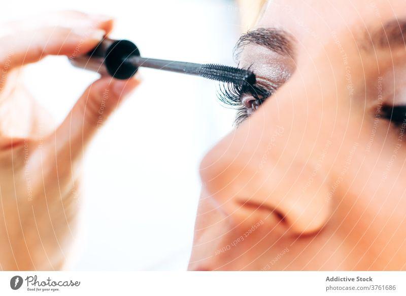 Crop-Visagist trägt Mascara auf Modell auf Wimperntusche Make-up Künstler bewerben Gesicht professionell Schönheit Produkt Verfahren Bürste Klient vorbereiten