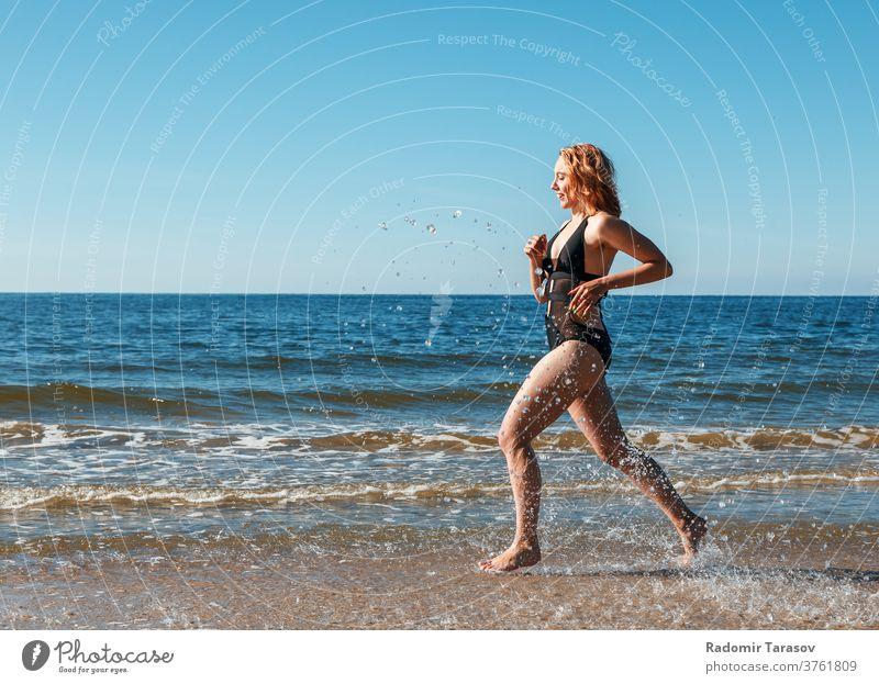 ein junges blondes Mädchen in einem schwarzen Badeanzug läuft am Sand des Meeresufers entlang Schönheit Kaukasier Körper schön Model Frau Wasser Person Sommer